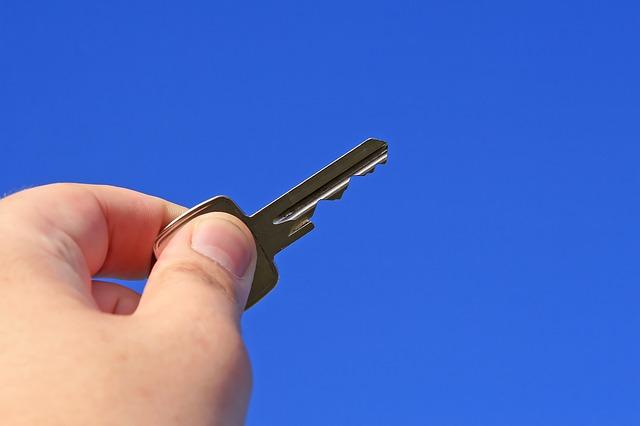 ruka, klíček, modré pozadí
