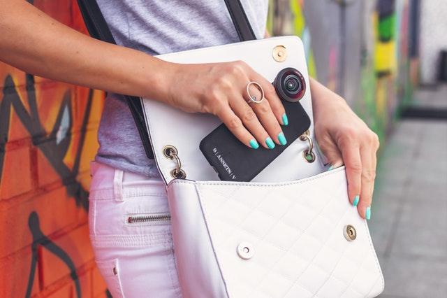 Detail ženské ruky vkládající telefon do bílé kabelky