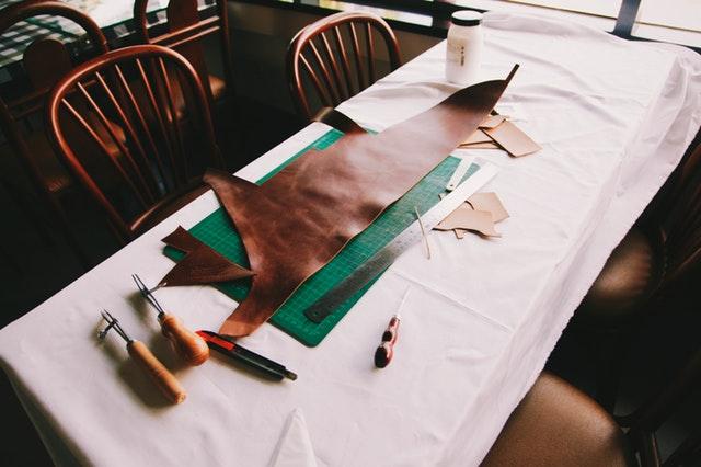 Kůže rozložená na stole společně s náčiním na její zpracování
